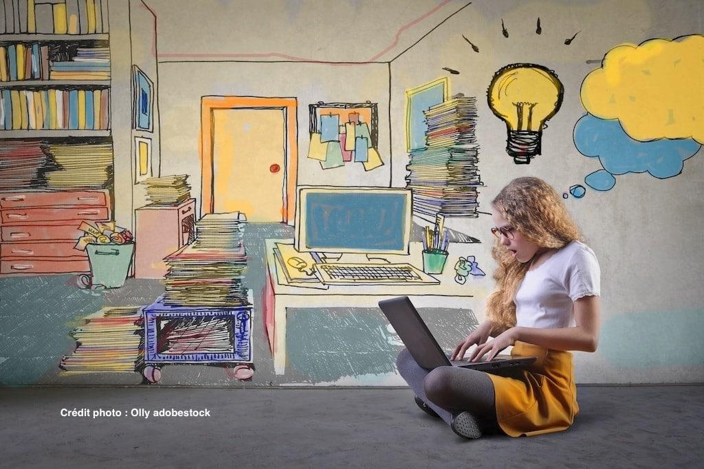 Jeune fille avec un portable en train de créer