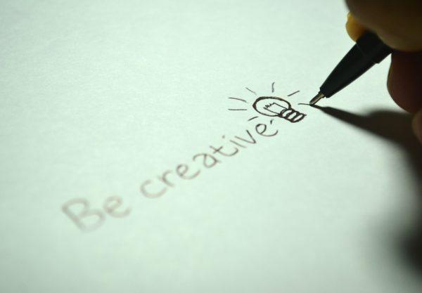 """Création numérique : Un crayon en train d'écrire sur une feuille de papier """"Be creative"""""""